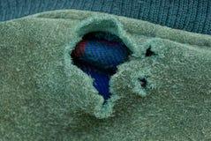 在老衣裳绿色织品的大被撕毁的孔  库存照片