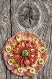 在老被打结的破裂的木野餐桌上的开胃菜美味盘集合 免版税库存图片