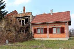 在老被破坏的房子旁边的未完成的新的郊区房子 免版税库存图片
