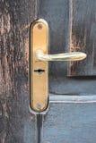 在老被风化的木门的金黄门把手 免版税库存照片