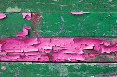 在老被风化的木头的削皮油漆与绿色和桃红色颜色削皮油漆构造了木背景 免版税库存图片