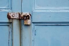 在老被绘的木门的生锈的挂锁 免版税图库摄影