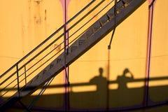 在老金属坦克的人阴影在能源厂, 免版税库存图片