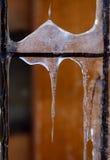 在老金属篱芭的冰柱 免版税图库摄影