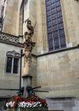 在老镇弗里堡,瑞士,欧洲授以爵位在喷泉的雕象哥特式St尼古拉斯大教堂外 免版税图库摄影
