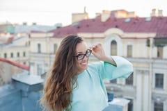在老镇的屋顶的晚上走一个年轻和美丽的女孩的画象有镜片的 概念的释放 库存图片