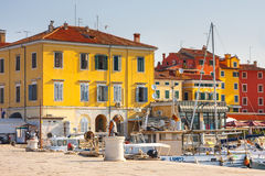 在老镇罗维尼的早晨视图从有室外餐馆的港口,克罗地亚 免版税库存图片