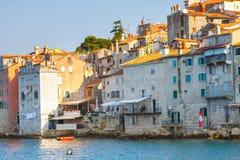 在老镇罗维尼的早晨视图从有室外餐馆的港口,克罗地亚 库存图片