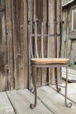 在老门廊的生锈的椅子 库存图片