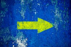 在老难看的东西和被风化的蓝色墙壁纹理背景绘的黄色箭头 库存照片