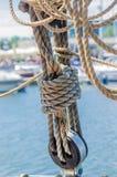 在老风船的索具以现代yac为背景 免版税库存照片