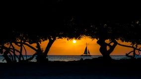在老鹰海滩,阿鲁巴的日落 海上的小船航行 库存照片