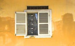 在老黄色墙壁上的葡萄酒窗口 免版税库存照片