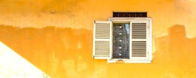 在老黄色墙壁上的葡萄酒窗口 图库摄影