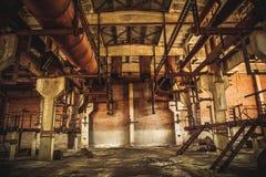 在老黑暗的难看的东西工厂厂房里面的被放弃的工业蠕动的仓库 免版税图库摄影