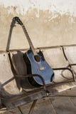 在老破旧的椅子的黑声学吉他 免版税库存图片