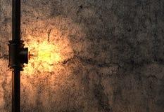 在老水泥墙壁上的电灯泡和金属管 图库摄影