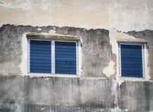在老水泥墙壁上的蓝色窗口 免版税库存图片