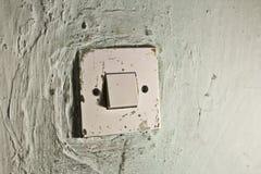 在老绿色墙壁上的老灯开关 库存图片
