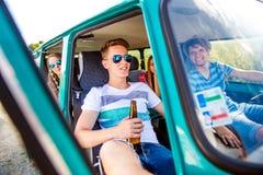 在老campervan,饮用的啤酒, roadtrip里面的少年 免版税图库摄影