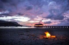 在考艾岛Hanalei海滩的日落与阵营火 免版税库存照片