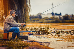 在耐心地坐一个的淡水湖的老人渔 库存图片