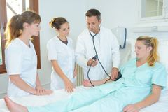 在耐心` s医院病床附近的医科学生 免版税库存图片