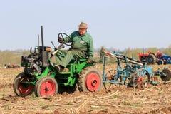 在耕的比赛的老绿色可信任的拖拉机 免版税库存图片
