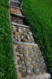 在耕种的草坪的路由各种各样的材料制成例如木头、石头或者腐土被划分对为训练使用的正方形脚 免版税库存照片