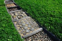 在耕种的草坪的路由各种各样的材料制成例如木头、石头或者腐土被划分对为训练使用的正方形脚 图库摄影