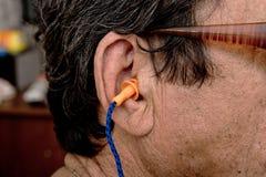 在耳朵的橙色耳塞在减少噪声的人 免版税库存照片