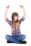 在耳机和跳舞的逗人喜爱的十几岁的女孩听的音乐 库存照片