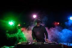 在耳机的专业非裔美国人的俱乐部DJ有混音器的 免版税库存照片