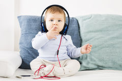 在耳机的可爱的男婴听的音乐。 免版税库存图片