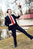 在耳机的商人跳舞 年轻人放松 自由职业者休息 免版税图库摄影