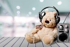 在耳机的在桌上的玩具熊和收音机 免版税库存照片