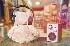 在耳机的在桌上的玩具熊和收音机 免版税图库摄影