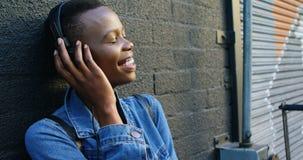 在耳机的妇女听的音乐,当倾斜对墙壁4k时 股票视频