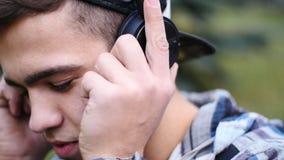 在耳机的年轻男性坐草和树,听的音乐 股票视频
