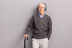 在耳机的老人听的音乐 库存照片