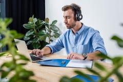 在耳机的被集中的商人与文件和膝上型计算机一起使用在办公室 免版税图库摄影