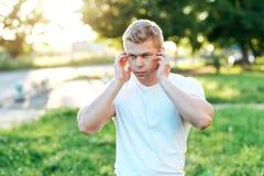在耳机的运动员教练员 在白色T恤杉 听audiobook,确信的神色 夏天生活方式,刺激 免版税库存图片