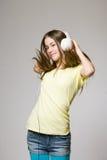 在耳机的逗人喜爱的青少年的跳舞。 免版税图库摄影