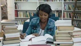 在耳机的Atractive非洲年轻女人听的音乐,当做某一笔记由大学的时笔记本 影视素材
