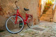 在耶路撒冷旧城的狭窄的街道上的红色自行车 库存照片