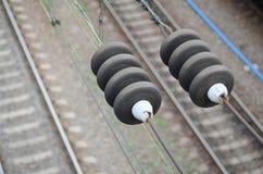 在联络导线的电子绝缘体在一条被弄脏的铁路轨道的背景 与有选择性的focu的宏观照片 图库摄影