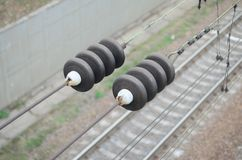 在联络导线的电子绝缘体在一条被弄脏的铁路轨道的背景 与有选择性的focu的宏观照片 免版税库存照片