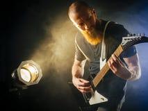 在聚光灯前面的吉他演奏员 免版税库存照片