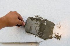 在聚苯乙烯泡沫塑料的工作者传播的灰浆与小铲 库存照片