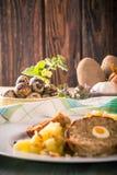 在肉饼旁边的部分的鹌鹑蛋在白色板材的用土豆泥 库存照片